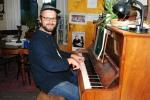 Espen ved pianoet i stua på Sandermosen Stasjon.